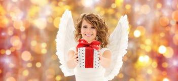 Mujer feliz con las alas del ángel y el regalo de la Navidad foto de archivo libre de regalías