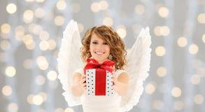 Mujer feliz con las alas del ángel y el regalo de la Navidad Foto de archivo