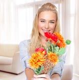 Mujer feliz con las flores en casa Imagenes de archivo