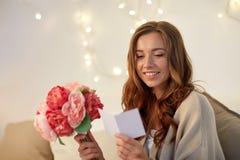 Mujer feliz con las flores y la tarjeta de felicitación en casa Imagenes de archivo