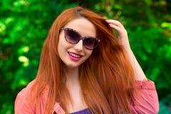 Mujer feliz con las gafas de sol que tocan el pelo Imagen de archivo