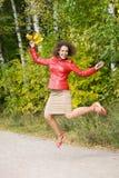 Mujer feliz con las hojas en salto en madera en otoño Foto de archivo