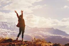 Mujer feliz con las manos aumentadas en el fondo de la puesta del sol del ` s de la montaña Foto de archivo