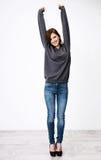 Mujer feliz con las manos aumentadas para arriba Foto de archivo