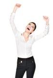 Mujer feliz con las manos aumentadas para arriba en la camisa blanca Imagen de archivo