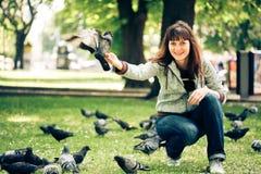 Mujer feliz con las palomas en parque Imagen de archivo libre de regalías