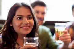 Mujer feliz con los amigos que beben la cerveza en el pub Fotografía de archivo