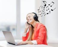 Mujer feliz con los auriculares que escucha la música Foto de archivo