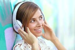 Mujer feliz con los auriculares que escucha la música Fotografía de archivo libre de regalías