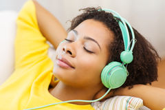 Mujer feliz con los auriculares que escucha la música Fotos de archivo