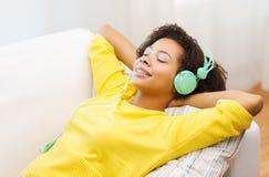 Mujer feliz con los auriculares que escucha la música Imagenes de archivo