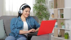 Mujer feliz con los auriculares que hojea el contenido del ordenador portátil metrajes