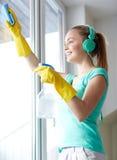 Mujer feliz con los auriculares que limpian la ventana imagen de archivo