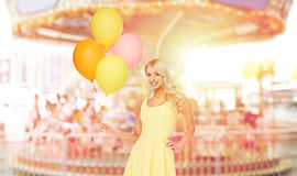 Mujer feliz con los balones de aire sobre el carrusel Foto de archivo libre de regalías
