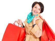 Mujer feliz con los bolsos de compras en capa beige del otoño Foto de archivo libre de regalías