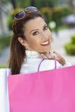Mujer feliz con los bolsos de compras rosados y blancos Fotos de archivo libres de regalías