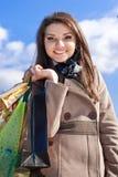 Mujer feliz con los bolsos de compras y el cielo azul Imagen de archivo libre de regalías