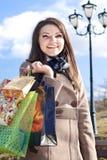 Mujer feliz con los bolsos de compras y el cielo azul Foto de archivo