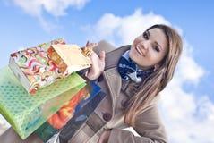 Mujer feliz con los bolsos de compras y el cielo azul Foto de archivo libre de regalías
