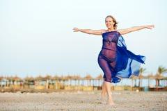 Mujer feliz con los brazos abiertos en la playa del mar Imagen de archivo