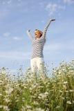 Mujer feliz con los brazos estirados en campo de flor Foto de archivo libre de regalías