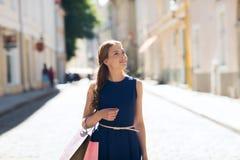 Mujer feliz con los panieres que camina en ciudad Foto de archivo