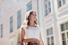 Mujer feliz con los panieres que camina en ciudad Fotografía de archivo