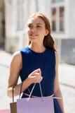 Mujer feliz con los panieres que camina en ciudad Fotografía de archivo libre de regalías