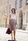 Mujer feliz con los panieres que camina en ciudad Foto de archivo libre de regalías