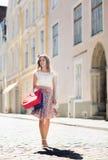 Mujer feliz con los panieres que camina en ciudad Imagen de archivo libre de regalías