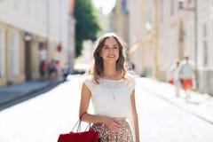 Mujer feliz con los panieres que camina en ciudad Fotos de archivo
