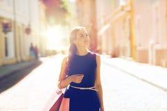 Mujer feliz con los panieres que camina en ciudad Imágenes de archivo libres de regalías
