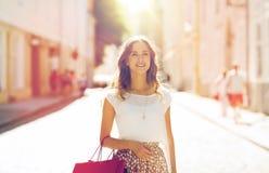 Mujer feliz con los panieres que camina en ciudad Imagen de archivo