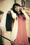 Mujer feliz con los panieres que invita al teléfono Fotos de archivo libres de regalías