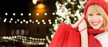 Mujer feliz con los panieres sobre el árbol de navidad Foto de archivo libre de regalías