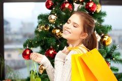 Mujer feliz con los panieres y el árbol de navidad Imagen de archivo