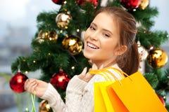 Mujer feliz con los panieres y el árbol de navidad Foto de archivo