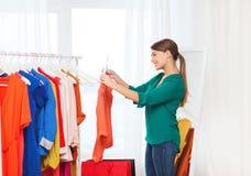 Mujer feliz con los panieres y la ropa en casa Imagen de archivo libre de regalías