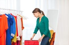 Mujer feliz con los panieres y la ropa en casa Foto de archivo libre de regalías