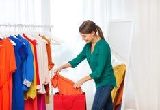 Mujer feliz con los panieres y la ropa en casa Fotografía de archivo libre de regalías