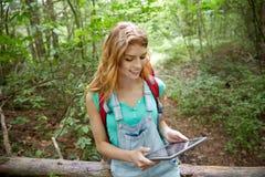 Mujer feliz con PC de la mochila y de la tableta en bosque Imagenes de archivo