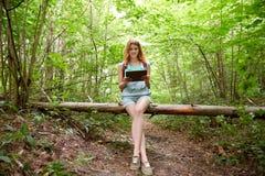 Mujer feliz con PC de la mochila y de la tableta en bosque Fotografía de archivo libre de regalías