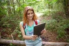 Mujer feliz con PC de la mochila y de la tableta en bosque Fotografía de archivo