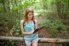 Mujer feliz con PC de la mochila y de la tableta en bosque Foto de archivo