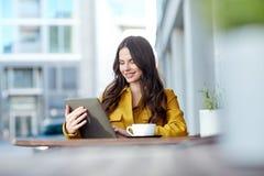 Mujer feliz con PC del cacao y de la tableta en el café de la ciudad Foto de archivo libre de regalías