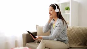 Mujer feliz con PC y los auriculares de la tableta en casa almacen de metraje de vídeo