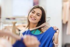 Mujer feliz con ropa en el espejo de la tienda de ropa Imagenes de archivo