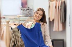 Mujer feliz con ropa en el espejo de la tienda de ropa Imagen de archivo