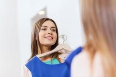 Mujer feliz con ropa en el espejo de la tienda de ropa Foto de archivo