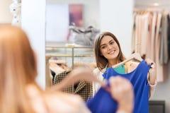 Mujer feliz con ropa en el espejo de la tienda de ropa Fotos de archivo libres de regalías